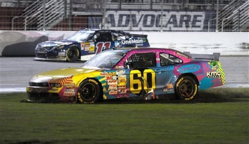 Driver Travis Pastrana (60) spins out through the infield on the final lap while Elliott Sadler (11) passes him during the Nationwide Series auto race at Atlanta Motor Speedway, Saturday, Aug. 31, 2013, in Hampton, Ga. (AP Photo/David Tulis)