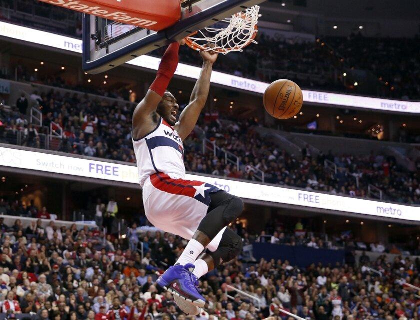 Washington Wizards guard John Wall dunks the ball in the second half of an NBA basketball game against the New York Knicks, Saturday, Oct. 31, 2015, in Washington. The Knicks won 117-110. (AP Photo/Alex Brandon)