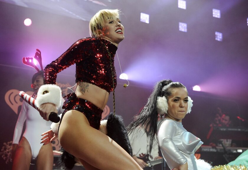 """FILE - This Dec. 6, 2013 file photo shows Miley Cyrus performing during the KIIS-FM Jingle Ball concert at Staples Center in Los Angeles. MTV has declared that Miley Cyrus is the best artist of the year. MTV said Monday, Dec. 9, that the VMA duet on """"We Can't Stop"""" and """"Blurred Lines"""" was the year'"""