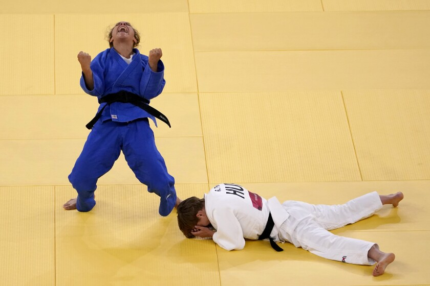 Odette Giuffrida, of Italy, left, reacts after defeating Reka Pupp, of Hungary, during a women's 52kg bronze medal judo match at the Tokyo 2020 Olympics, Sunday, July 25, 2021, in Tokyo. (AP Photo/David Goldman)