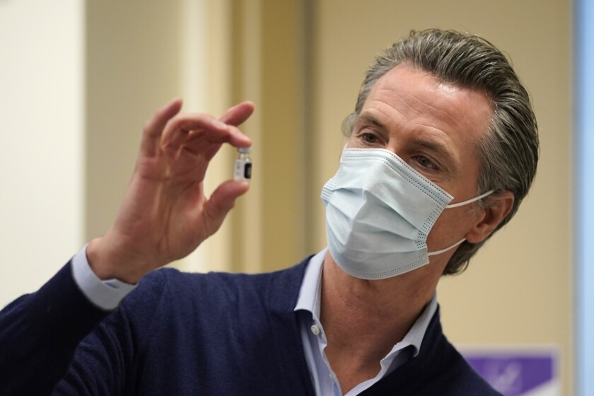 Gov. Newsom, masked, holds a vial of a coronovirus vaccine.