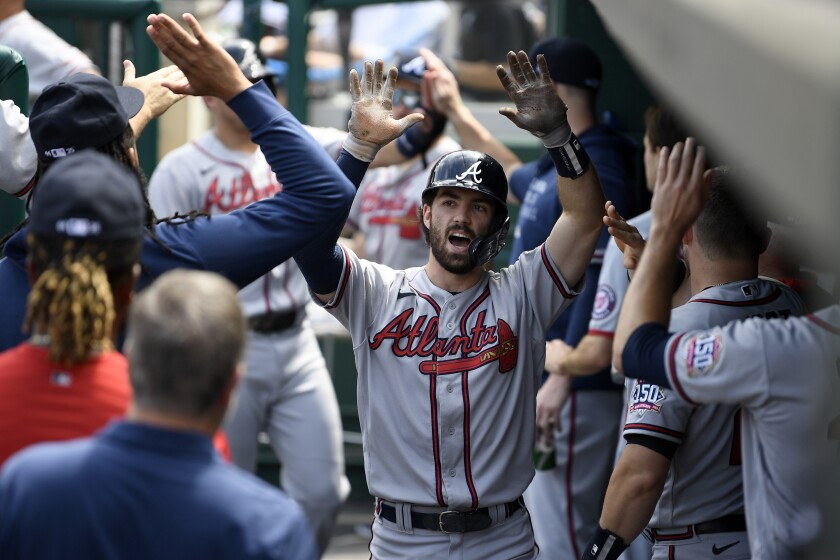 Atlanta Braves' Dansby Swanson celebrates his two-run home run in the dugout during the third inning of a baseball game against the Washington Nationals, Sunday, Aug. 15, 2021, in Washington. (AP Photo/Nick Wass)