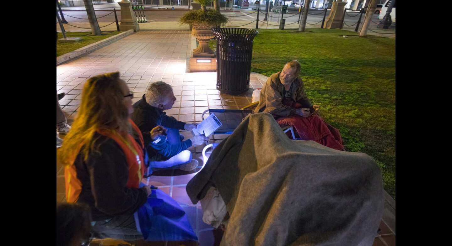 Jill Kernes, homeless outreach coordinator for the Downtown San Diego Partnership Clean and Safe Program, left, and Bill Geppert, center, a volunteer, conduct a point-in-time survey with John Ross, right, a homeless man, sleeping near the fountain in Horton Plaza, during the annual homeless count, before sunrise.