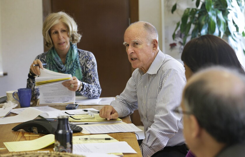 Gov. Jerry Brown discusses a bill while meeting with advisors at his Capitol office in Sacramento. At left is advisor Nancy McFadden.