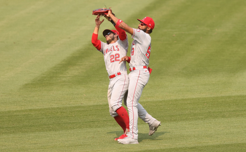 Angels second baseman David Fletcher, left, and right fielder Jo Adell collide while catching a fly ball.