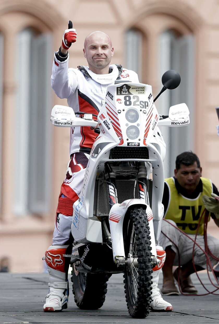 In this Sunday, Jan. 4 photo, Michal Hernik of Poland posses for a picture as he crosses the podium ramp during the symbolic start of the Dakar Rally 2015 in Buenos Aires, Argentina, 2015. According to race authorities Hernik was found dead during the third stage of the race between the cities of S