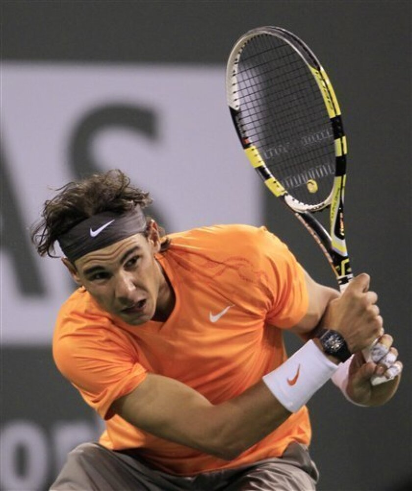 Rafael Nadal of Spain hits a return to Rik De Voest of South Africa during a second round match at the BNP Paribas Open tennis tournament in Indian Wells, Calif., Saturday, March 12, 2011. Nadal won 6-0, 6-2. (AP Photo/Darron Cummings)