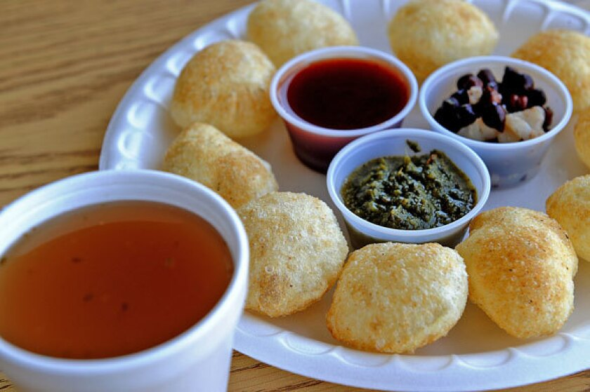 The pani puri, fluffed flour crisps, are served with spicy water, spicy sauce, sweet sauce, garbanzos and potatoes.