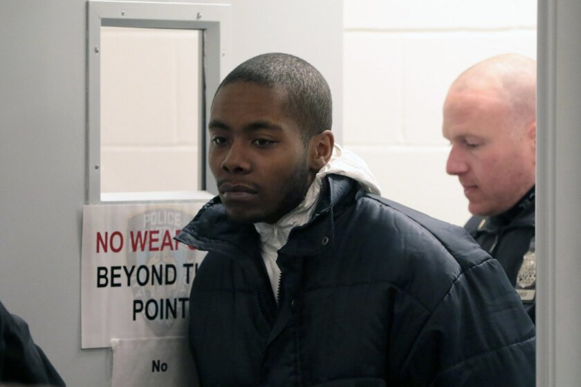 Michael Sykes is led into the courtroom to be arraigned, Sunday, Feb. 14, 2016 at criminal court in the Staten Island borough of New York. Police on Saturday arrested Sykes, a fugitive suspected of stabbing his girlfriend and all three of her small children with a kitchen knife in a brutal attack a