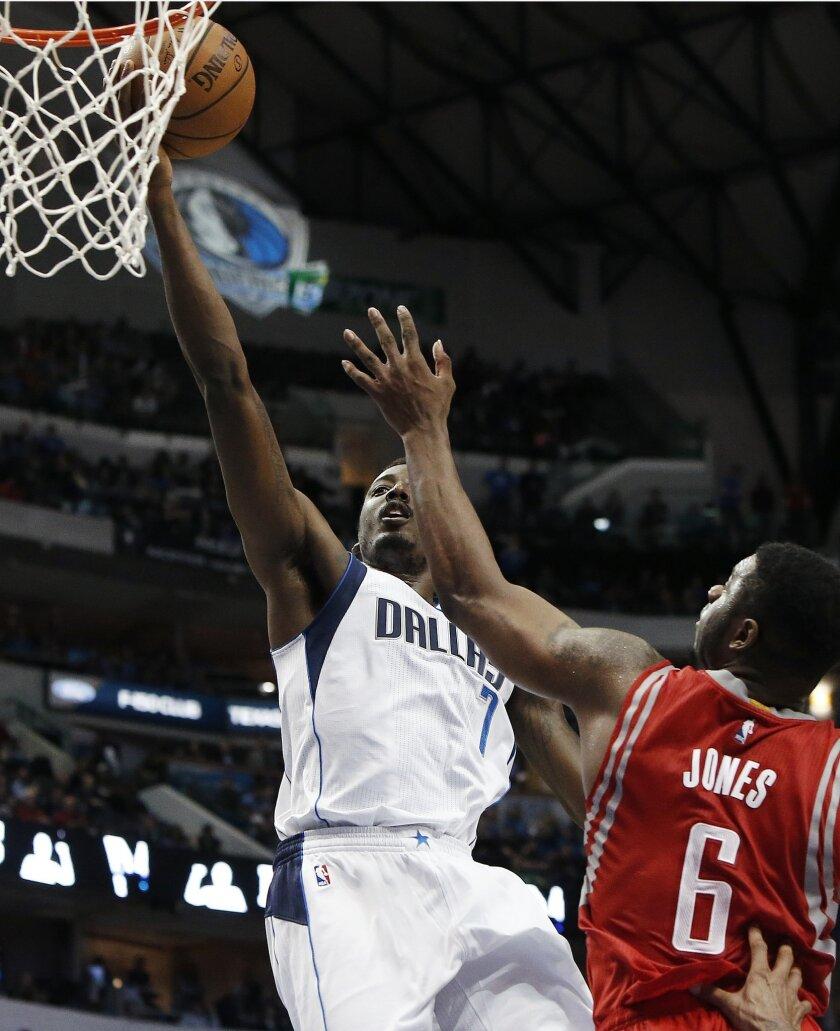 Dallas Mavericks forward Al-Farouq Aminu (7) shoots as Houston Rockets forward Terrence Jones (6) defends during the second half of an NBA basketball game, Friday, Feb. 20, 2015, in Dallas. Dallas won 111-100. (AP Photo/Brandon Wade)