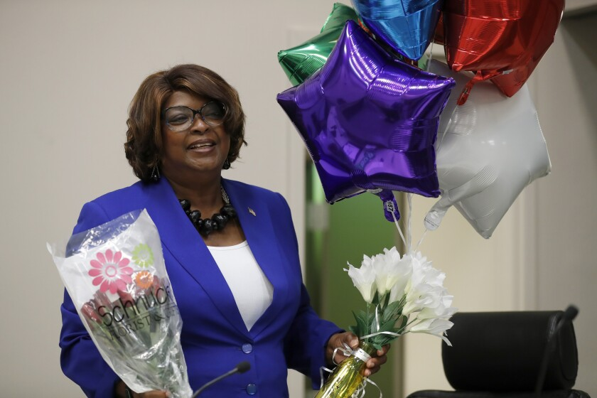 Mayor Ella Jones, right, holds balloons and flowers after being sworn in Tuesday, June 16, 2020, in Ferguson, Mo. Jones becomes the first black and first woman to become mayor of Ferguson, the city thrust into the national spotlight after the death of Michael Brown in 2014, replacing James Knowles III, who was prohibited form seeking a fourth term due to term limits. (AP Photo/Jeff Roberson)