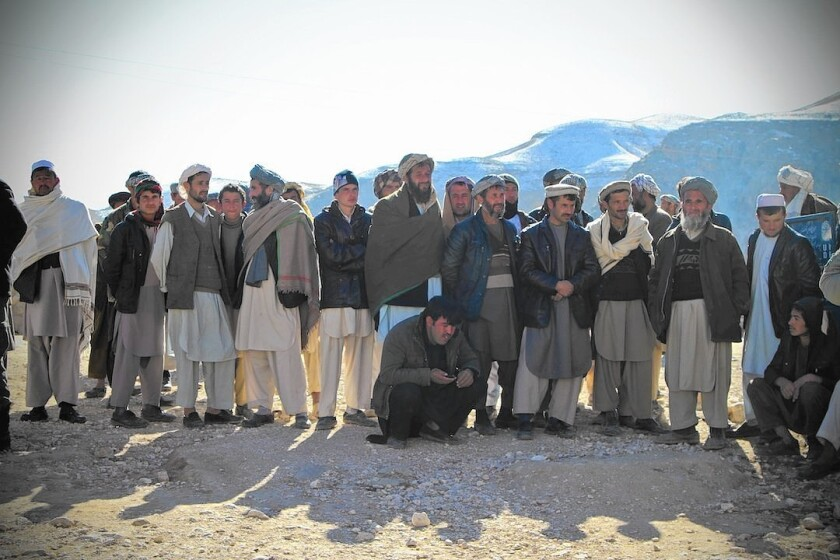 Afghan men in Samangan province wait for the distribution of aid packages, an effort led by First Lady Rula Ghani.