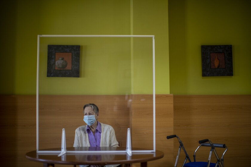 A resident awaits the visit of her family behind glass meant to protect against COVID-19 at DomusVi nursing home in Leganes, Spain, Wednesday, March 10, 2021. Spain is preparing to tighten some pandemic restrictions on movement during the approaching Easter holiday, which is a traditional period for family visits. (AP Photo/Manu Fernandez)