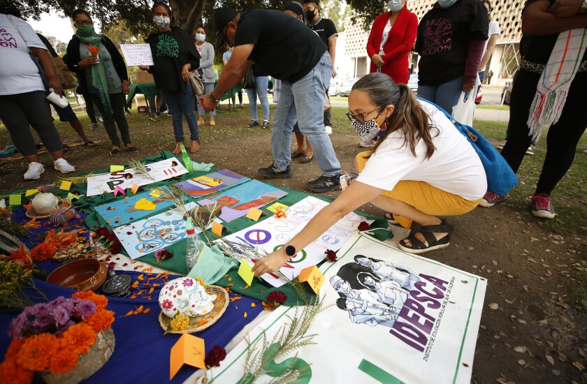 A woman places a card on an altar set up on the ground at a domestic workers protest at a park