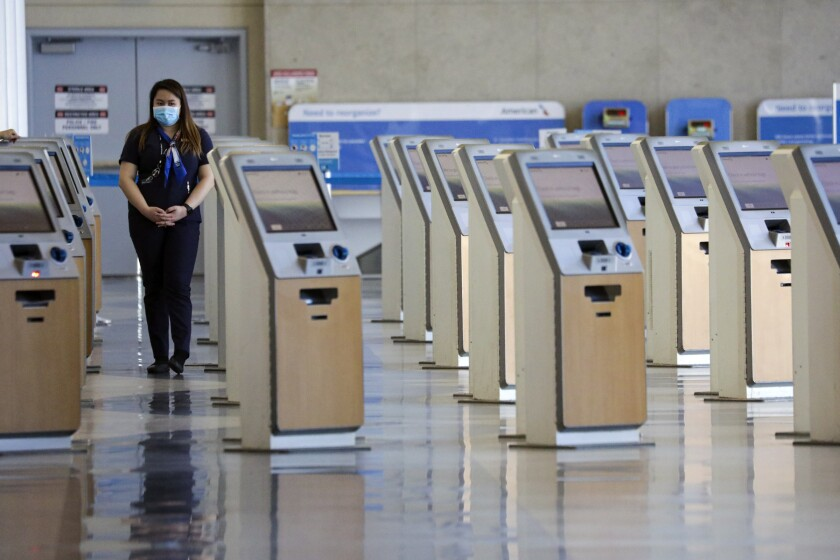 A worker with American Airlines stands among unused ticketing kiosks at Los Angeles International Airport in May.