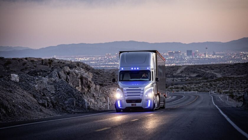A driver operates a Freightliner truck on a road outside Las Vegas. Freightliner parent Daimler AG is investing more than half a billion dollars into driverless technology.
