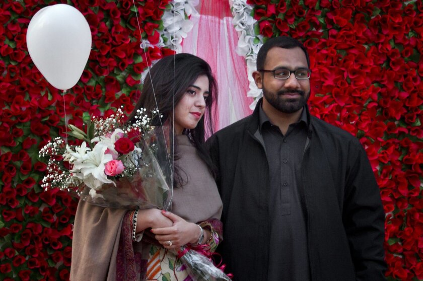 A couple pose for photograph in front of a giant heart-shaped bouquet displayed by a vendor to attract customers on Valentine's Day in Islamabad, Pakistan, Sunday, Feb. 14, 2016. Celebrating Valentine's Day is considered un-Islamic by some in Pakistan, but many still buy flowers and exchange gifts