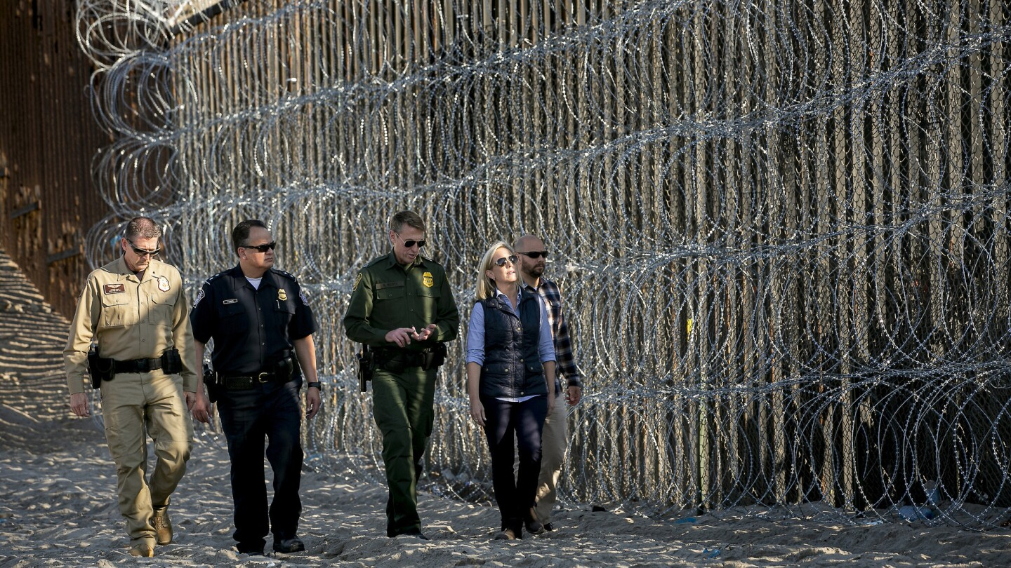 Secretary of Homeland Security Kirstjen Nielsen tours the U.S.-Mexico border fence under the gaze of a mass of cameras at Border Field State Park.