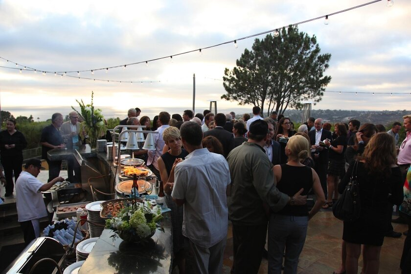 Attendees at a fundraiser for Parkinson's patients enjoy food and the setting sun at the home of Jeffrey Strauss, owner of the Pamplemousse Grill. The proceeds help Summit4StemCell.org.