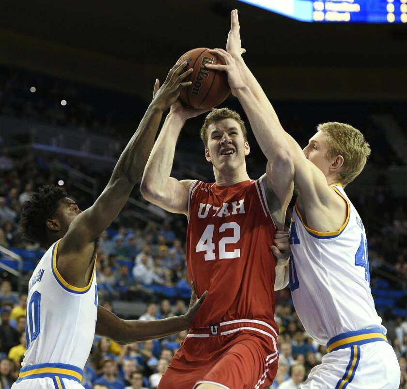 Utah forward Jakob Poeltl, center, attempts a shot between UCLA guard Isaac Hamilton, left, and center Thomas Welsh, right, during the first half of an NCAA basketball game, Thursday, Feb. 18, 2016, in Los Angeles. (AP Photo/Kelvin Kuo)