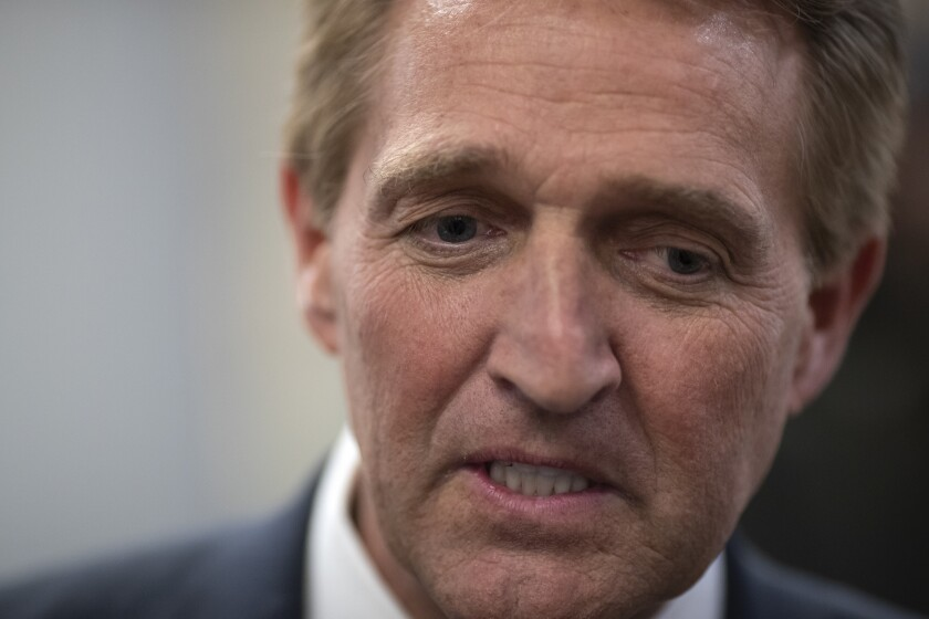 """FILE - In this Nov. 14, 2018, file photo, then-Sen. Jeff Flake, R-Ariz., speaks with reporters at the Capitol in Washington. Republicans are facing a reckoning as they contend with some divisive candidates during the country's struggle through civic unrest. """"He's driving away moderate Republicans and independents en masse,"""" Flake, who retired last year after clashing with Trump, said in an interview Wednesday, June 3, 2020. """"For Republicans who need to appeal to a broader base, it's devastating."""" (AP Photo/J. Scott Applewhite, File)"""