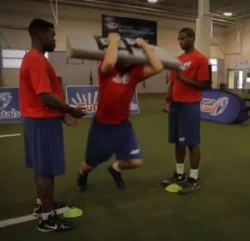 A screen grab from a training video demonstrates a 'rip' maneuver of Heads Up Tackle. During a traditional tackle, players stick their heads out and wrap their arms around their opponent, while in a 'rip,' the arms go up in an uppercut move. usafootball.com