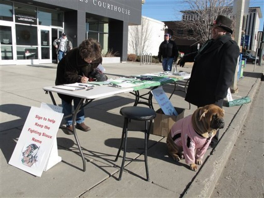 Charles Tuttle, a backer of the University of North Dakota's Fighting Sioux nickname, watches as a woman signs petitions supporting the nickname on Tuesday, Feb. 7, 2012, in front of the federal courthouse in Bismarck, N.D. Nickname advocates planned to turn in the petitions to Secretary of State Al Jaeger before midnight Tuesday, hoping they had enough signatures to force a statewide vote on whether the University of North Dakota in Grand Forks, N.D., should have to keep the Fighting Sioux nickname despite the possibility of NCAA sanctions. The NCAA considers the nickname and a university American Indian logo to be racially offensive. The dog is Tuttle's Italian cane corso, Bella. (AP Photo/Dale Wetzel)