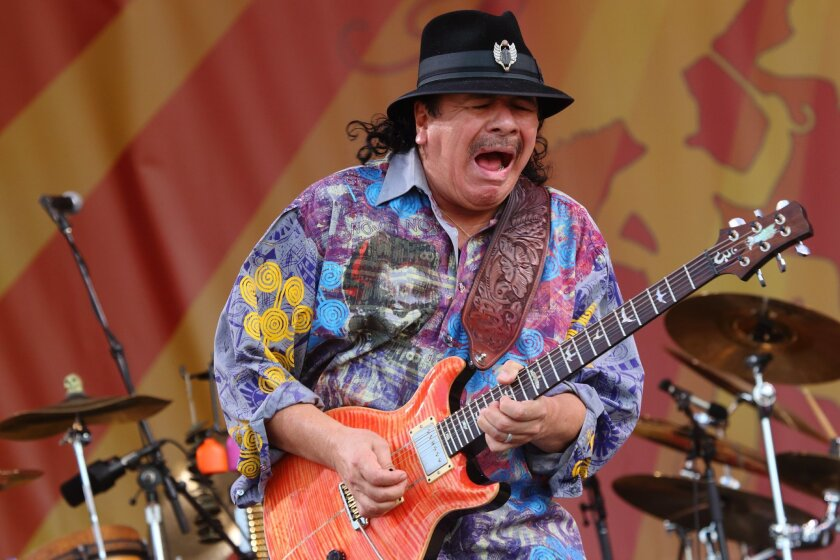"""FILE - This April 25, 2014 file photo shows Carlos Santana performing at the 2014 New Orleans Jazz & Heritage Festival in New Orleans. Santana's latest album, """"Corazon,"""" debuted at No. 9 on the Billboard 200 albums chart last week. It features Juanes, Gloria Estefan and Miguel, and Santana said it wasn't hard finding """"Cinderella or Cinderfella"""" to guest on the songs, which he calls """"glass slippers."""" (Photo by John Davisson/Invision/AP, File)"""