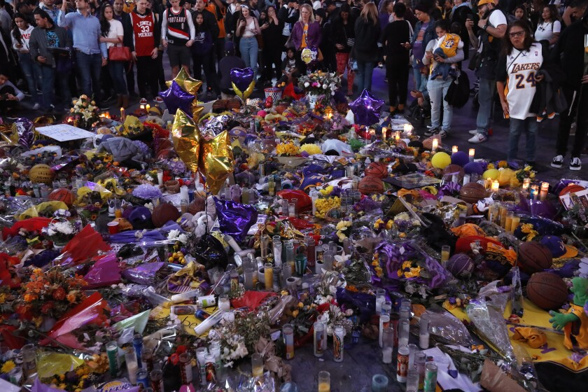 Fans visit a makeshift memorial for Lakers legend Kobe Bryant at L.A. Live on Friday prior to a game between the Lakers and Portland Trail Blazers at Staples Center on Friday.