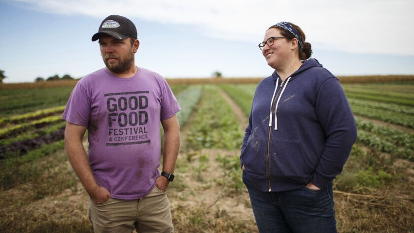 PrairiErth Farm owners Hans, left, and Katie Bishop in the field at their farm near downstate Atlanta, Ill. The Bishops left comfortable jobs in the insurance industry to start their farm.