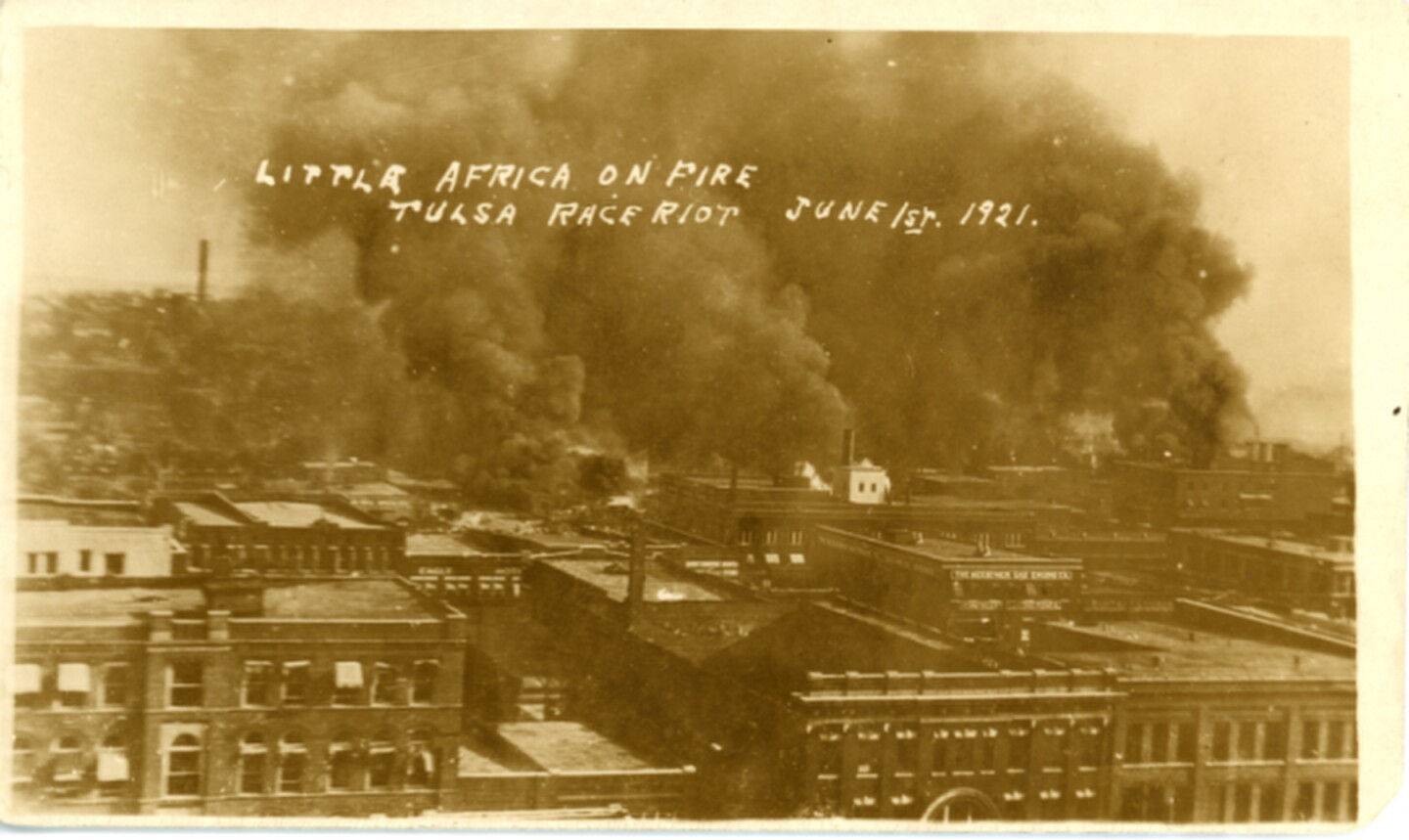 "The burning Greenwood District during the Tulsa Race Massacre, 1921. First Street is visible in the foreground on which is located the Bessemer Gas Engine Company and the Eagle Hotel. The back of the photograph contains a notation stating, ""Building in foreground with arched front - Tulsa Opera House on 2nd between Boston and Cincinnati. 113 E. 2nd St."""