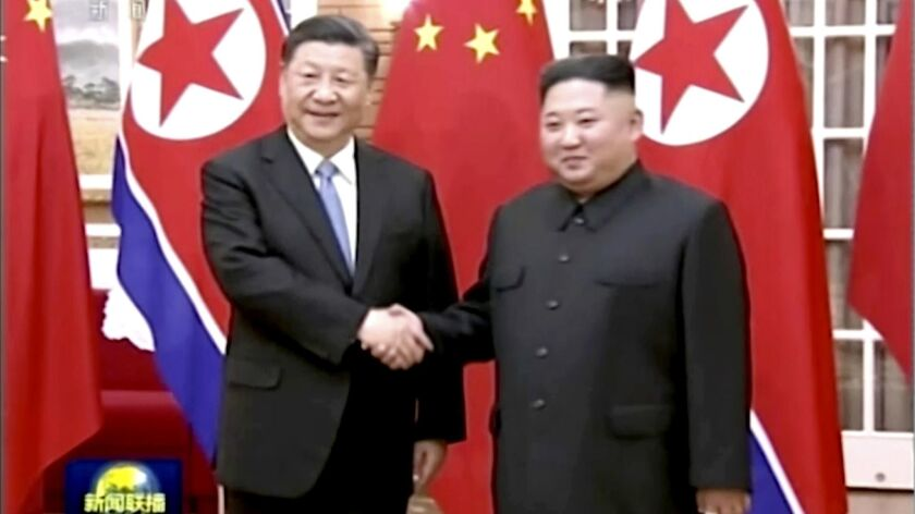 In this image taken from a video footage run by China's CCTV, Chinese President Xi Jinping, left, an