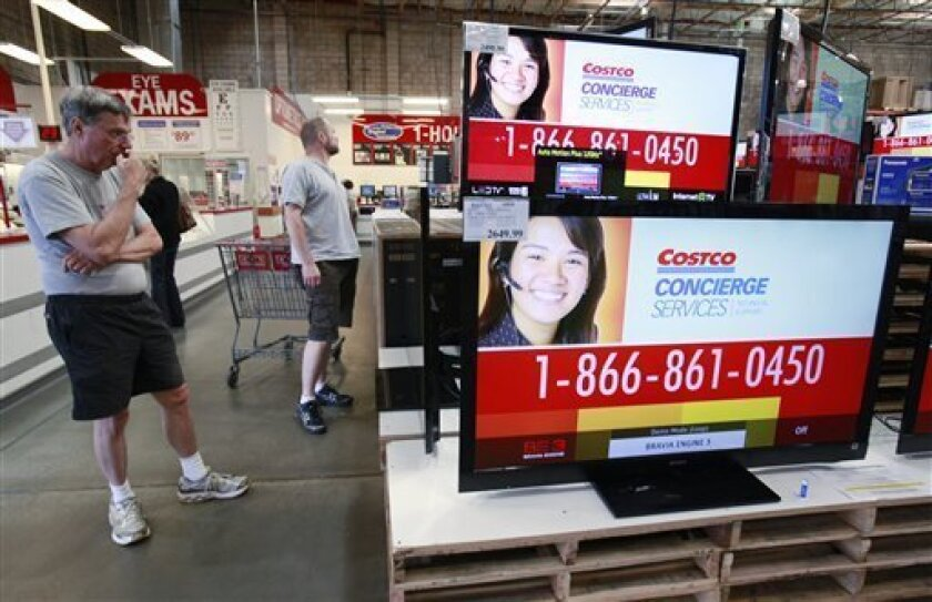 FILE - This file photo taken May 4, 2010 shows customers looking at wide screen TV sets Costco store in Mountain View, Calif. Inventories held by wholesalers rose for a fourth straight month in April while sales rose for a 13th consecutive time. Both gains were encouraging signs pointing to a sustained economic recovery. (AP Photo/Paul Sakuma, file)