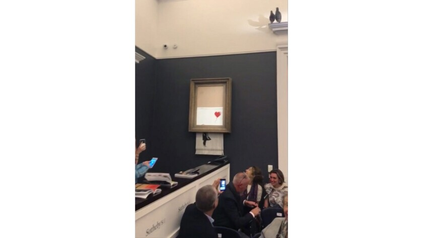 "People watch as the spray-painted canvas ""Girl with Balloon"" by artist Banksy is shredded at Sotheby's in London."