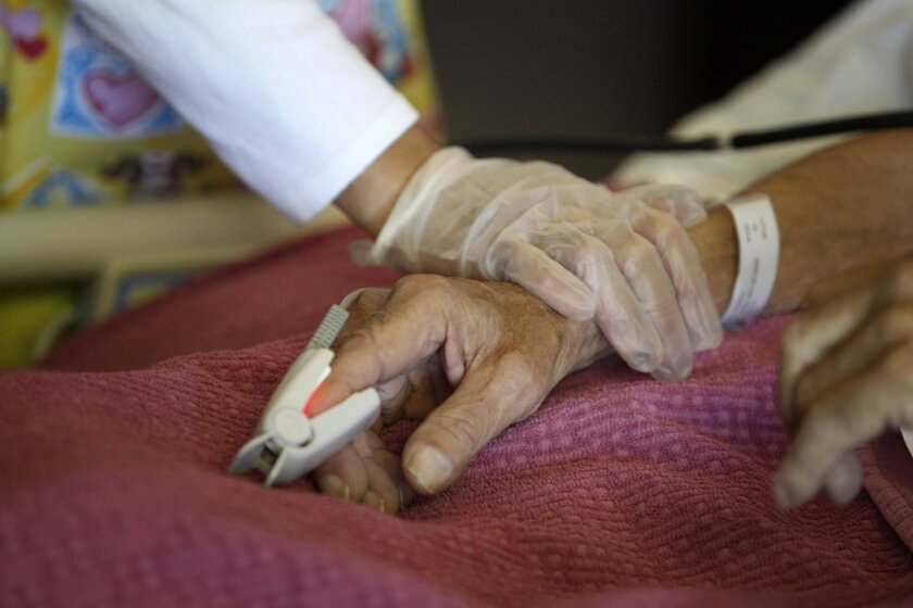 Nurse Cherry Miller checks the vital signs of a patient at San Diego Hospice in 2012.