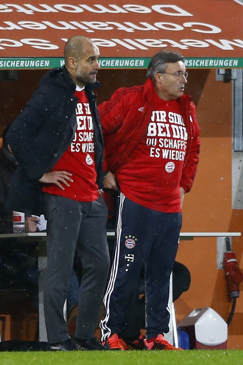 Bayern head coach Pep Guardiola, left, watches his team during the German first division Bundesliga soccer match between FC Augsburg and FC Bayern Munich at the WWK Arena in Augsburg, Germany, Sunday, Feb. 14, 2016. (AP Photo/Matthias Schrader)