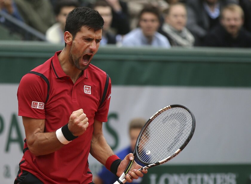 Serbia's Novak Djokovic clenches his fist as he plays Austria's Dominic Thiem during their semifinal match of the French Open tennis tournament at the Roland Garros stadium, Friday, June 3, 2016 in Paris. (AP Photo/Michel Euler)