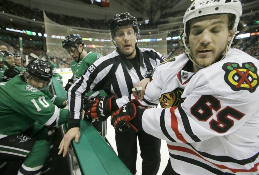 Linesman Darren Gibbs (66) pulls Chicago Blackhawks center Andrew Shaw (65) away from the Dallas Stars bench including Patrick Sharp (10) and Mattias Janmark during the first period of an NHL hockey game Saturday, Feb. 6, 2016, in Dallas. (AP Photo/LM Otero)