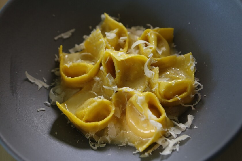 """Tortellini in Brodo """"al contrario"""" features tortellini filled with hot broth. The diced mortadella and Parmesan cheese are in the sauce, rather than in the pasta."""