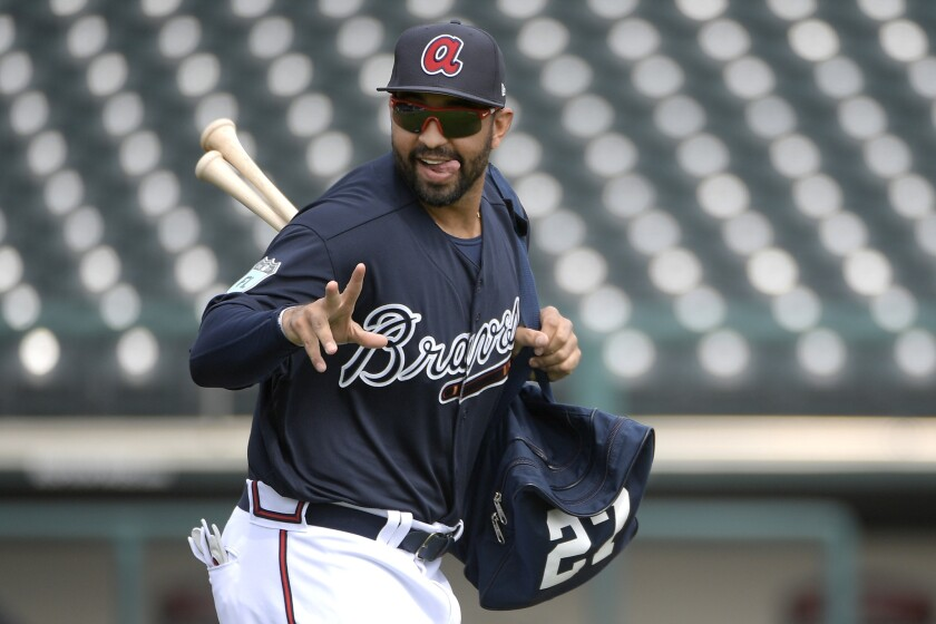 Atlanta Braves outfielder Matt Kemp acknowledges fans in the stands while jogging onto the field during the first full-squad spring training workout in Lake Buena Vista, Fla., Saturday, Feb. 18, 2017. (AP Photo/Phelan M. Ebenhack)