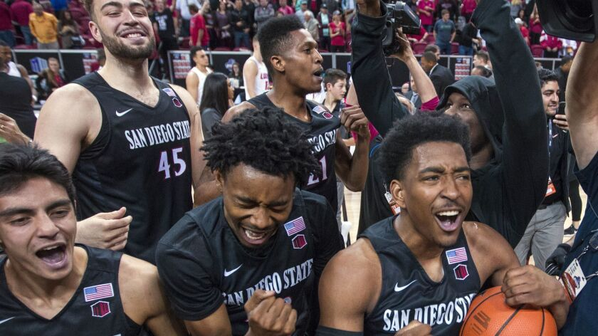 San Diego State players celebrate an 82-75 win over New Mexico in an NCAA college basketball game fo
