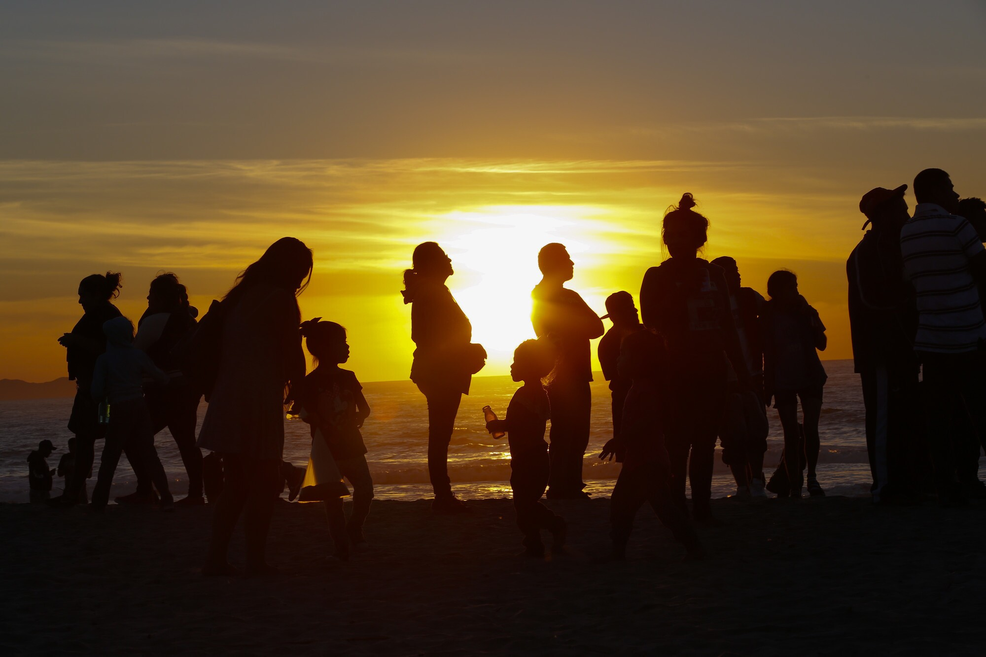 A group of Central American migrants silhouetted by the sunset at the beach by the border fence