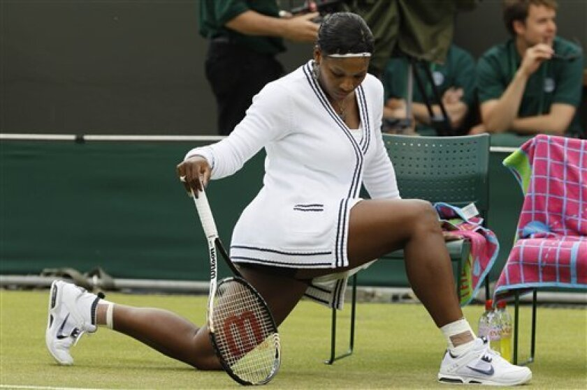 Serena Williams of the US stretches before the match against Romania's Simona Halep at the All England Lawn Tennis Championships at Wimbledon, Thursday, June 23, 2011. (AP Photo/Alastair Grant)