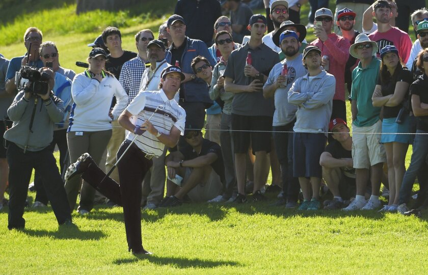 Bubba Watson makes his approach shot on the 18th fairway during the third round of the Northern Trust Open golf tournament, Saturday, Feb. 20, 2016, in the Pacific Palisades section of Los Angeles. (AP Photo/Mark J. Terrill)