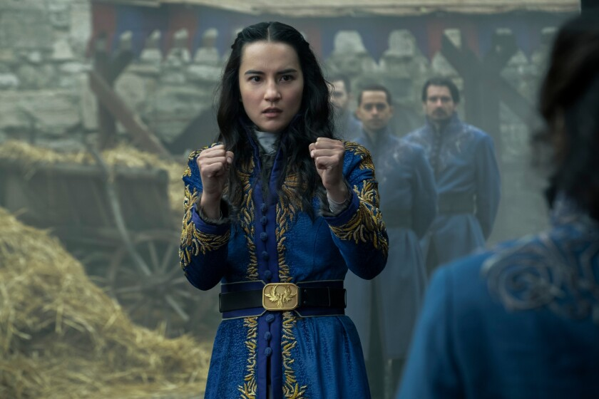 A young woman in a blue and gold dress puts her fists up prepared to fight