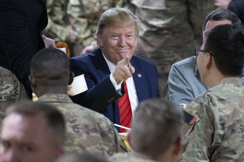 President Trump smiling and pointing toward the camera at Bagram Airfield in Afghanistan on Nov. 28, 2019. In the foreground, U.S. soldiers stand before him.