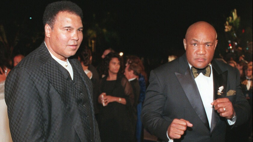 Muhammad Ali, left, and George Foreman arrive at the Vanity Fair Oscar party in Los Angeles on March 24, 1997.