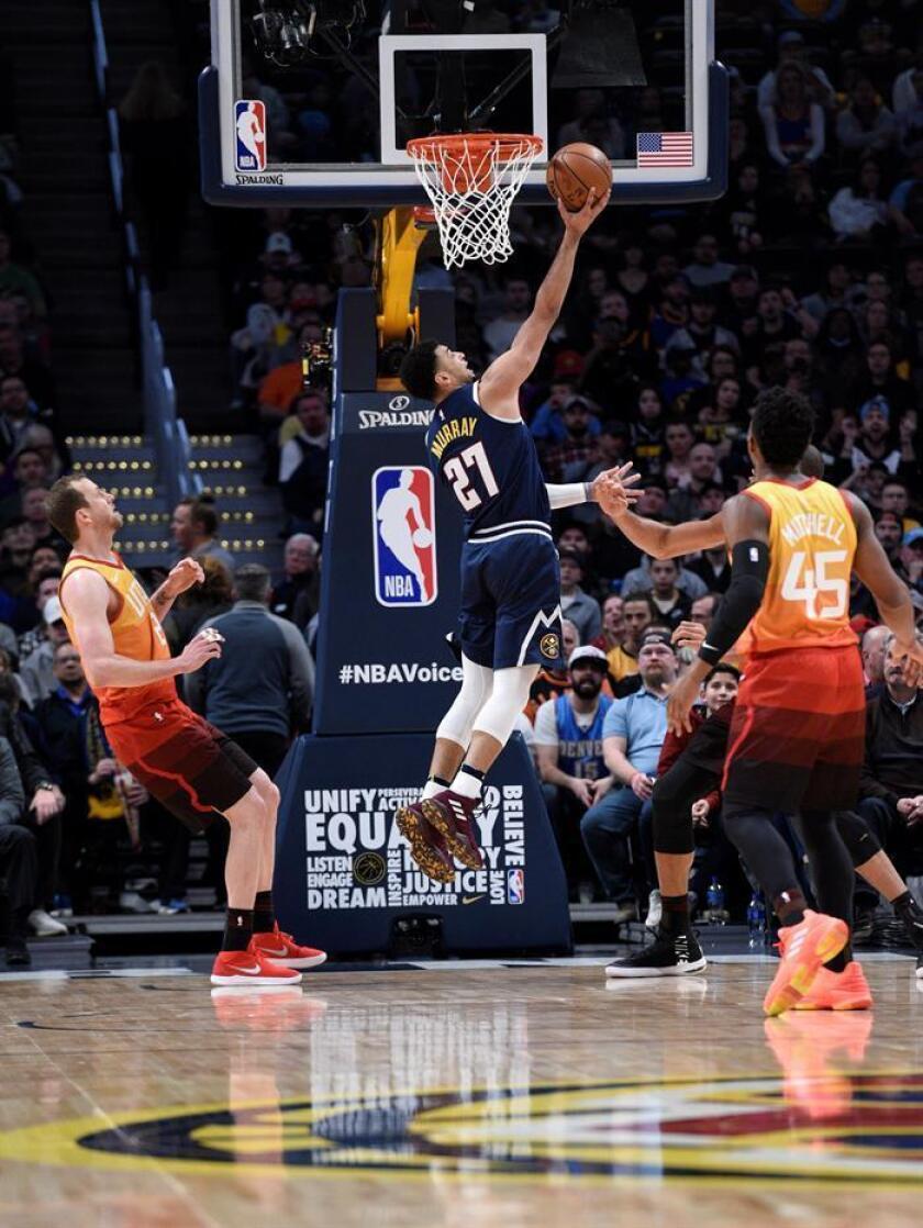 Jamal Murray (c) de Denver Nuggets intenta anotar ante Joe Ingles (i), y Donovan Mitchell (d), este viernes durante un juego de la NBA entre Denver Nuggets y Utah Jazz, en el Pepsi Center en Denver (Estados Unidos). EFE