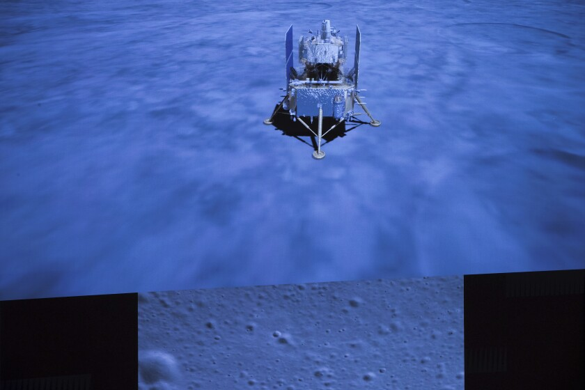 A display screen in Beijing shows the China's Chang'e-5 spacecraft and an image of the moon's surface taken by the craft