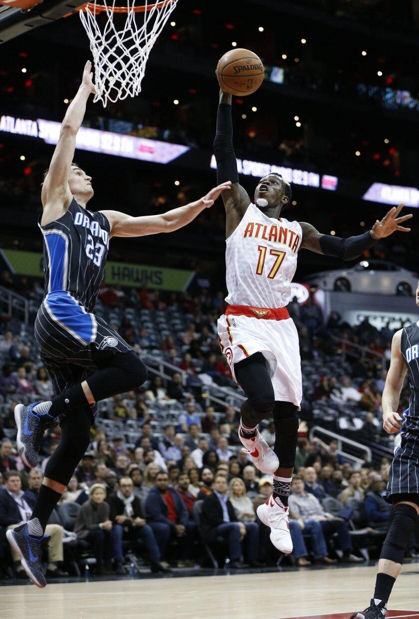 Atlanta Hawks guard Dennis Schroder (17) scores against Orlando Magic guard Mario Hezonja (23) in the first half of an NBA basketball game Monday, Feb. 8, 2016, in Atlanta. (AP Photo/John Bazemore)